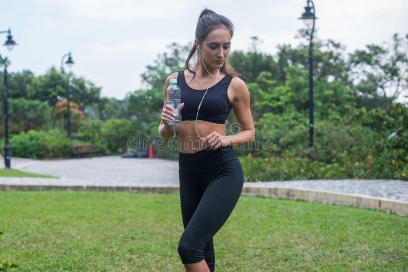 Pełny długość strzał piękny sprawności fizycznej kobiety model w czarnej sportswear pozyci na trawie w miasto parku i słuchanie zdjęcia royalty free