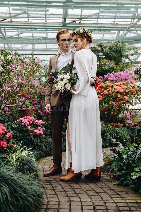 pełny długość widok piękna młoda elegancka ślub para stoi wpólnie między kwiatami obrazy royalty free