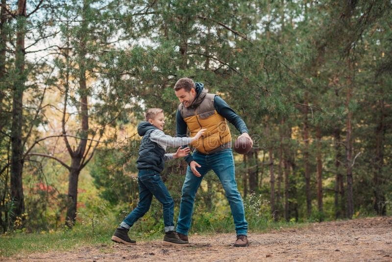 pełny długość widok szczęśliwy ojciec i syn bawić się z rugby piłką fotografia royalty free