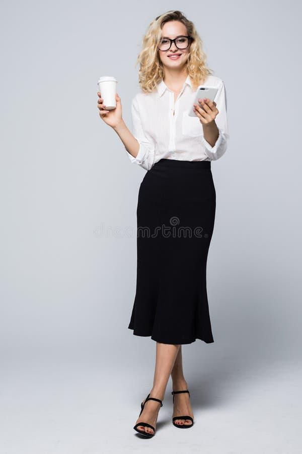 Pełny długość wizerunek ładna biznesowa kobieta w formalnej odzieży pozycji i używać telefon komórkowy z takeaway kawą wewnątrz o fotografia stock
