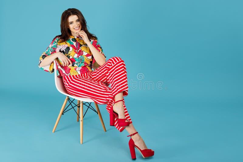 Pełny długość wizerunek ładna brunetki kobieta siedzi na krześle na błękitnym tle w kolorowych przypadkowych ubraniach obrazy stock