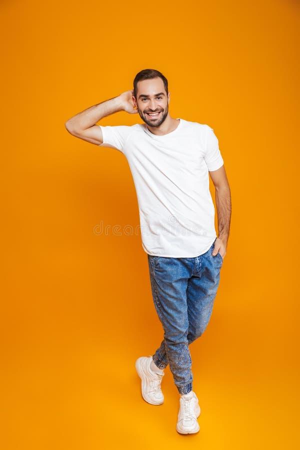 Pełny długość wizerunek atrakcyjny mężczyzna 30s z brodą i wąsy ono uśmiecha się podczas gdy stojący, nad żółtym tłem obraz royalty free