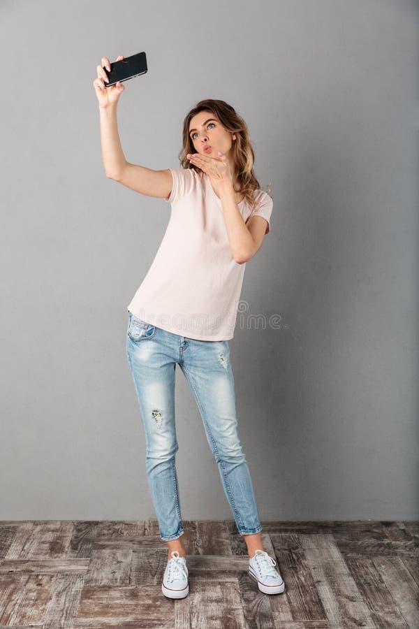 Pełny długość wizerunek Figlarnie kobieta w koszulce robi selfie obrazy royalty free