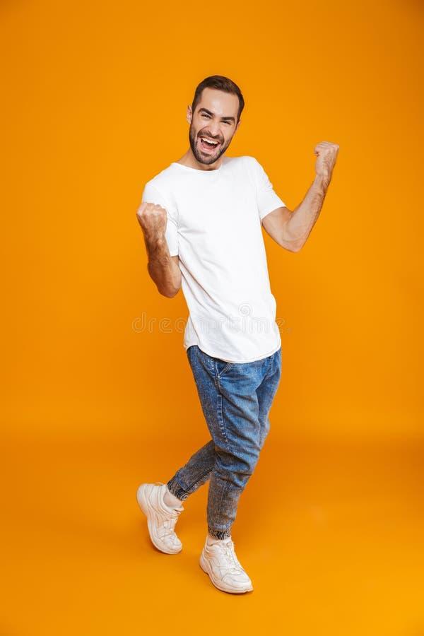 Pełny długość wizerunek optymistycznie facet 30s w koszulce i cajgach zaciska pięści podczas gdy stojący, nad żółtym tłem zdjęcia royalty free