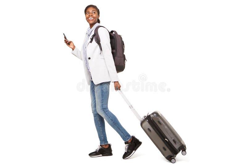 Pełny długości strony portret szczęśliwy młody murzynki odprowadzenie z bagażem i telefonem komórkowym obraz stock