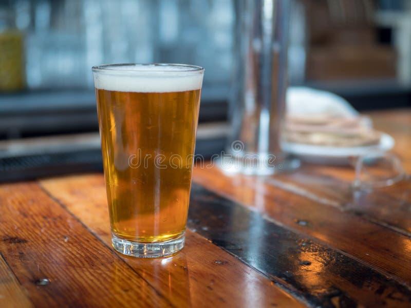 Pełny pół kwarty szkło piwny obsiadanie na baru kontuarze fotografia royalty free