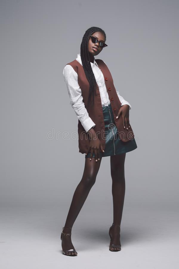 Pełny wzrost Młoda przypadkowa afrykańska kobieta w okularach przeciwsłonecznych i szpilkach odizolowywających na szarym tle zdjęcie royalty free