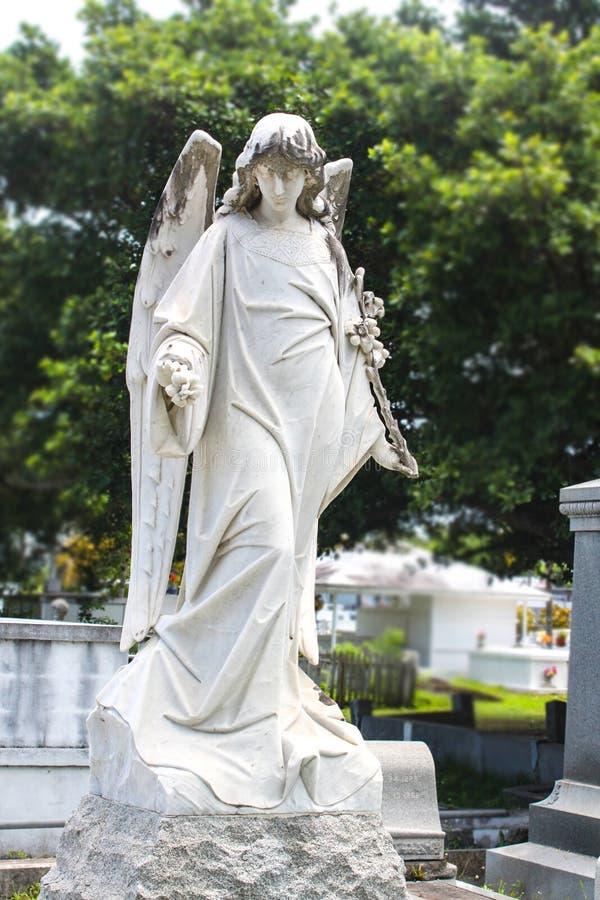 Pełnych rozmiarów dorosłej kobiety anioł z kwiatami w cmentarzu z drzewami nad grób za ona i zdjęcie royalty free