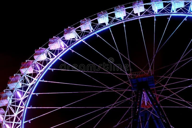 Pe?a da roda de ferris com ilumina??o roxa na noite foto de stock royalty free