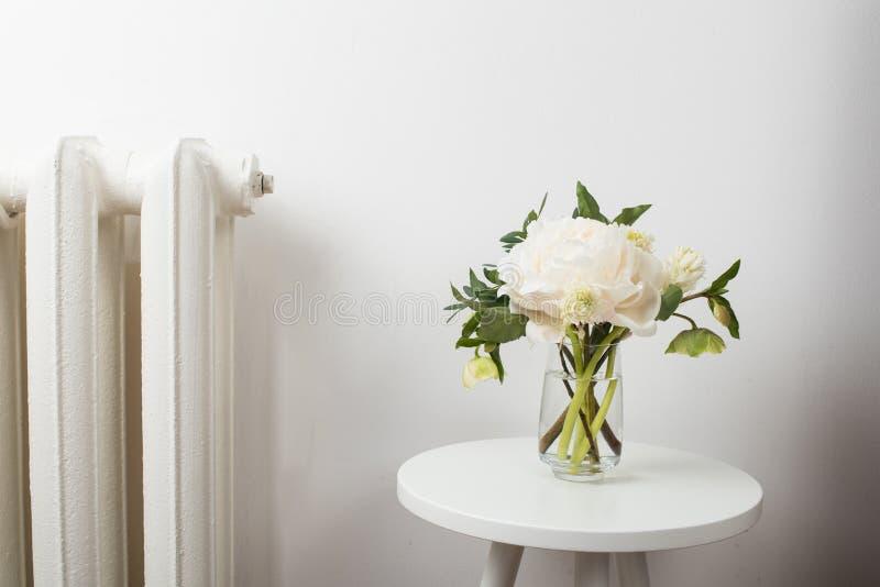 A peônia branca floresce na mesa de centro no interior da sala branca fotografia de stock royalty free