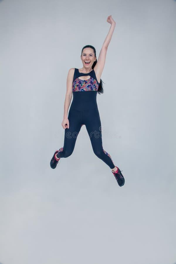 Pe?ny d?ugo?? portret m?oda sprawno?ci fizycznej kobieta w sportswear pozuje i skacze odizolowywaj?cy nad szarym t?em fotografia stock