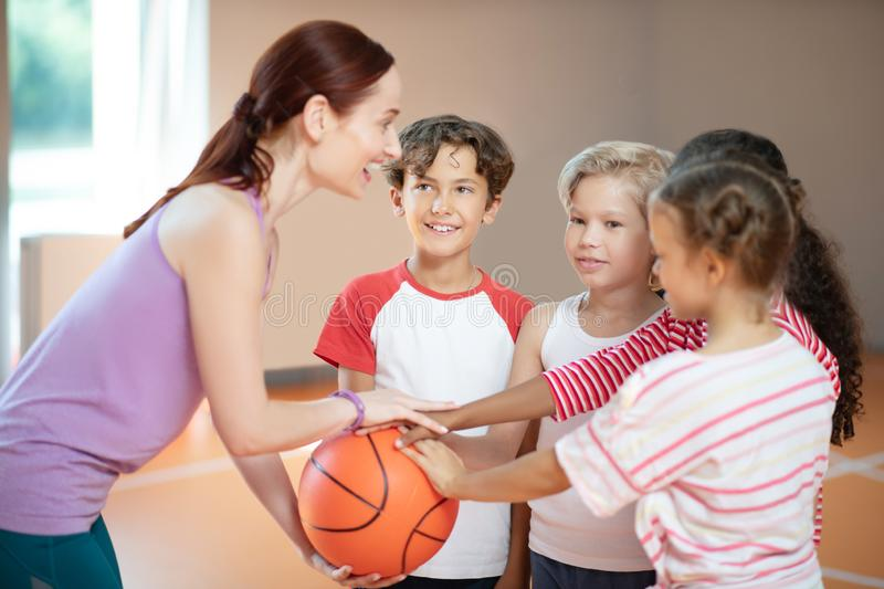 PE teacher and children smiling before starting basketball game. Before basketball game. PE teacher and children smiling before starting basketball game at PE stock photo
