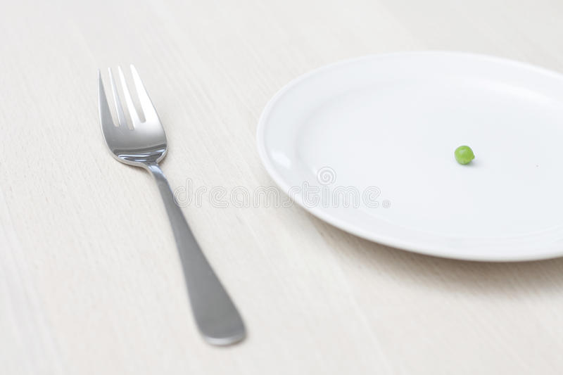 Pea. A single green pea on a plate royalty free stock image
