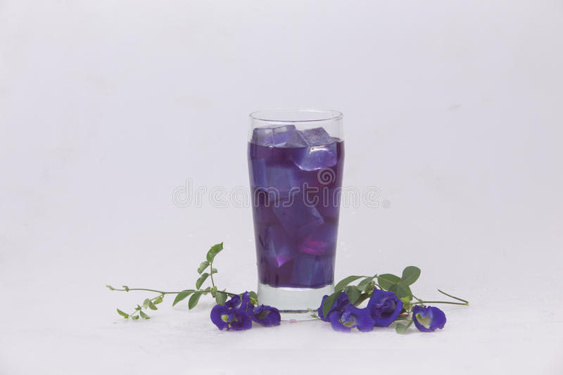 A pea in a glass with ice. Refreshing thirst quencher. Crake herbs in a glass of water with ice. Refreshing thirst quencher Against the backdrop of white stock image