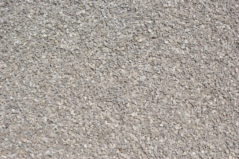 Pea gravel of crushed stone, for construction purposes. Individual pieces are sharply angular, and the gravel is heaped loosely stock images