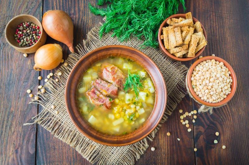 Pea Soup Traditionell soppa med ärtor, grönsaker och rökte stöd tjänade som i en keramisk platta spelrum med lampa Selektivt foku royaltyfri foto