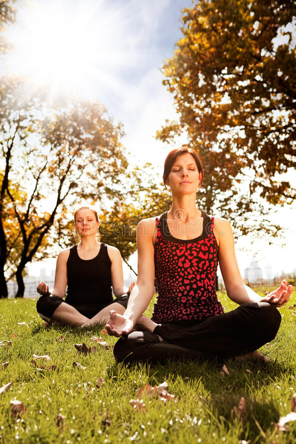 Peace. A group of people meditating in a city park stock photo