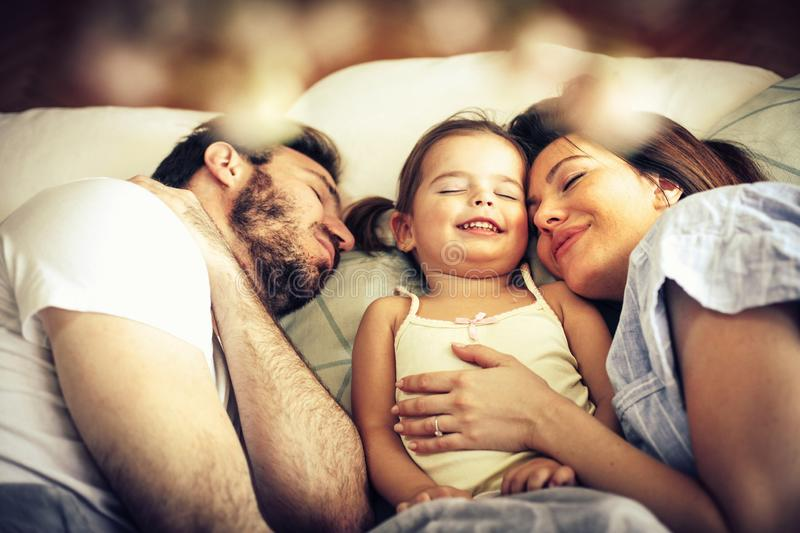 Peace and blessings. Young family sleeping together in bed stock photo