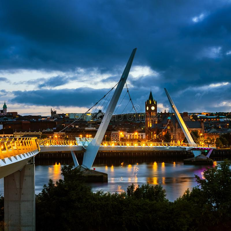 Peace bridge in Derry Londonderry in Northern Ireland with city center. Derry, Ireland. Illuminated Peace bridge in Derry Londonderry in Northern Ireland with royalty free stock image