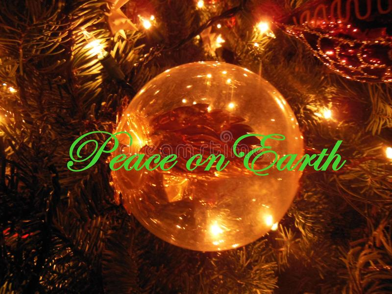 Peace on Earth. Holiday Greetings on Christmas tree, wishing all Peace on Earth. Ornament on tree stock photo
