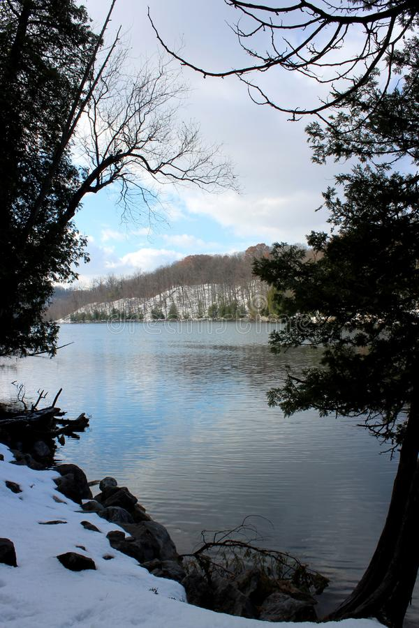 Peace-filled scene of clear blue-green lake water, with trees, and freshly fallen snow along banks stock image