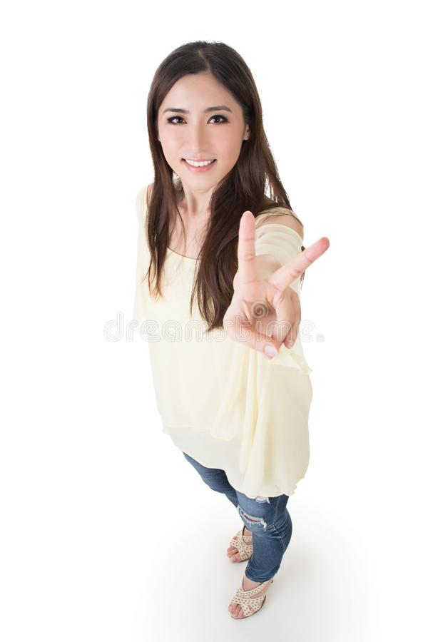 Peace gesture. Asian woman give you a sign of peace, full length portrait isolated on white background royalty free stock photo