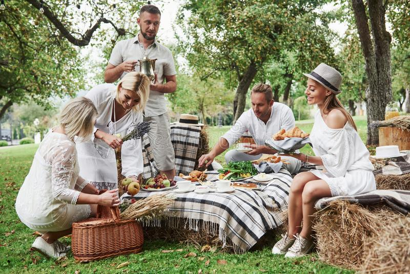 Peace and good mood. Group of adult friends have a rest and conversation in the backyard of restaurant at dinner time royalty free stock image