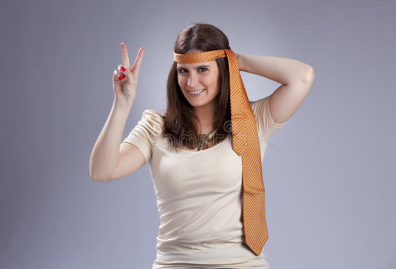 Peace and love. Young woman with a necktie on her head, gesturing the peace and love sign with her fingers stock photo