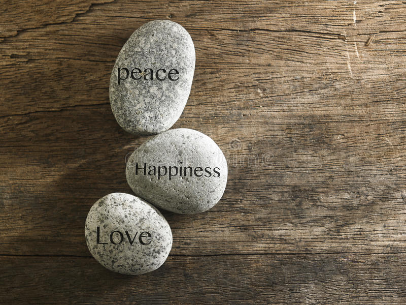 Peace love happiness. Pebbles or stone with inspirational text Peace, love, happiness stock photo