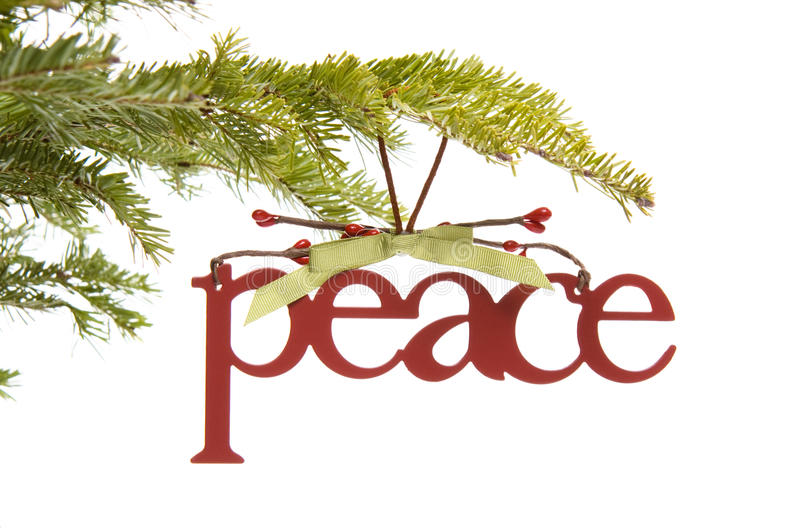 Peace ornament on Christmas tree branch. A peace ornament hanging from a Christmas tree branch isolated on white royalty free stock photo