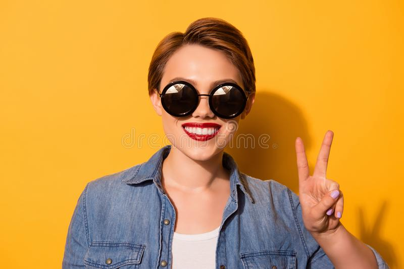 Peace! Portrait of a playful young stylish girl. She is in a jeans shirt and has a bright red lips, standing on the yellow royalty free stock photography