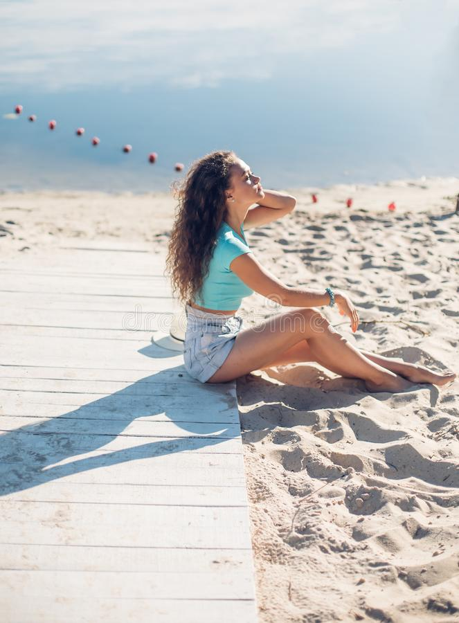 Peace and relaxation beautiful curly girl sitting on the beach. model in profile. vacation mood woman thinking and looking away stock image