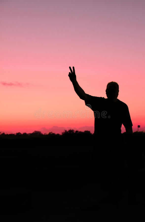 Peace sign. Silhouette of a man doing peace sign with his fingers stock photos