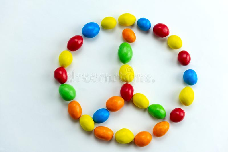 Peace sign made from bright multicolored candies. Top view flat lay on a white background stock photography