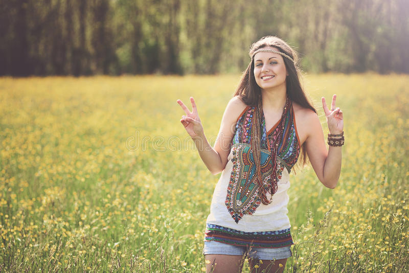 Peace sign from smiling hippie. In a meadow. Freedom and harmony stock photo