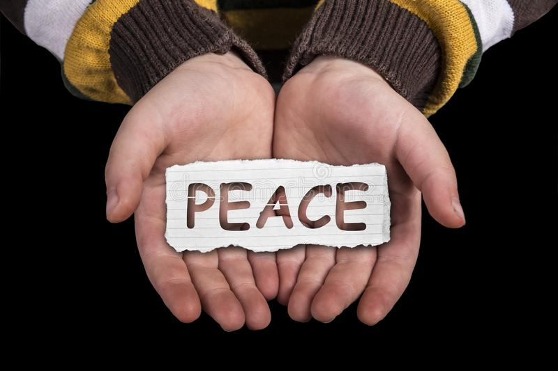 Peace text on hand. Peace text in line paper on child hand on black background stock photo