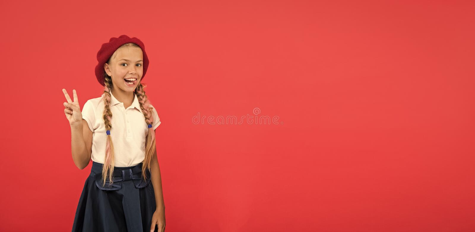 Peace to all. Little kid wearing stylish french beret. Cute girl having trendy hairstyle. Small child with long hair. Plaits. Fashion girl with tied hair into stock photo
