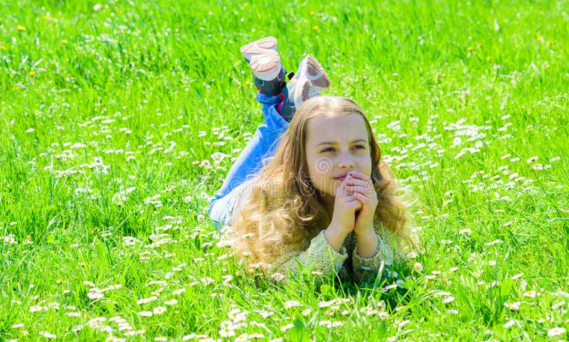 Peace and tranquil concept. Girl on hopeful dreamy face spend leisure outdoors. Child enjoy spring sunny weather while. Lying at meadow. Girl lying on grass at stock images