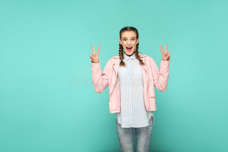 Peace or victory portrait of beautiful cute girl standing with m. Akeup and brown pigtail hairstyle in striped light blue shirt pink jacket. indoor, studio shot stock image