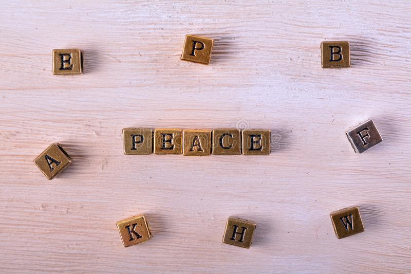 Peace word metal block. Peace word gold and silver metal block on white wood with letter blocks around stock photos