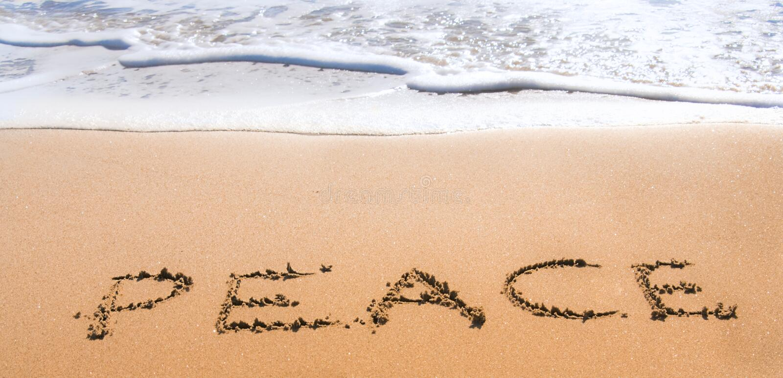 Peace written in sand on beach royalty free stock photography