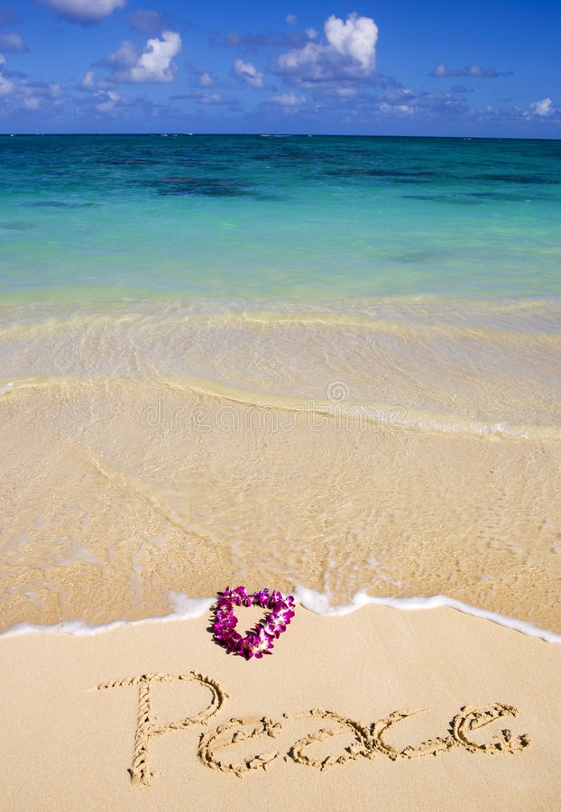 Peace written in the sand on a beach. On a beach in Hawaii, the word peace is written in the sand as the water flows toward it and the orchid lei that sits with stock photo