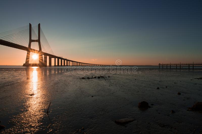 Beautiful sunrays at Vasco de Gama Bridge in Lisbon. Ponte Vasco de Gama, Lisboa, Portugal. Peaceful atmosphere at Vasco de Gama Bridge in Lisbon during sunrise stock photo