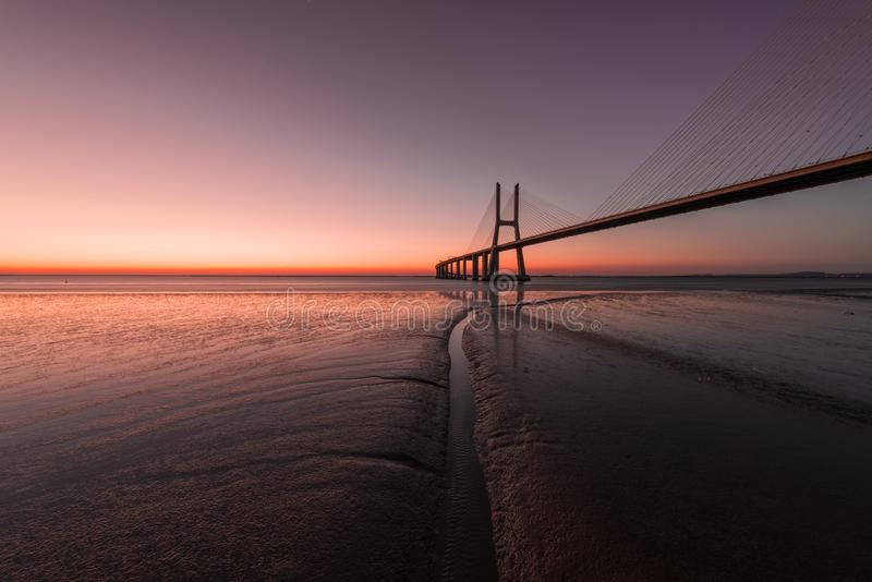 Pink atmosphere at Vasco de Gama Bridge in Lisbon. Ponte Vasco de Gama, Lisboa, Portugal. Peaceful atmosphere at Vasco de Gama Bridge in Lisbon during sunrise royalty free stock image