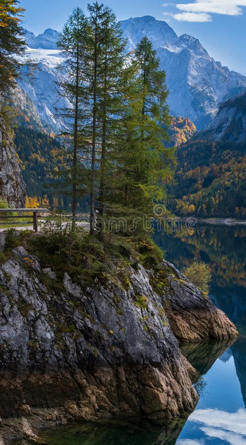 Peaceful autumn Alps mountain lake with clear transparent water and reflections. Gosauseen or Vorderer Gosausee lake, Upper. Sunny idyllic colorful autumn alpine royalty free stock image