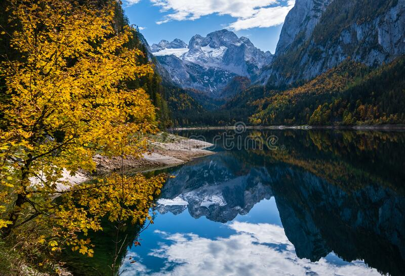 Peaceful autumn Alps mountain lake with clear transparent water and reflections. Gosauseen or Vorderer Gosausee lake, Upper. Sunny idyllic colorful autumn alpine royalty free stock photo