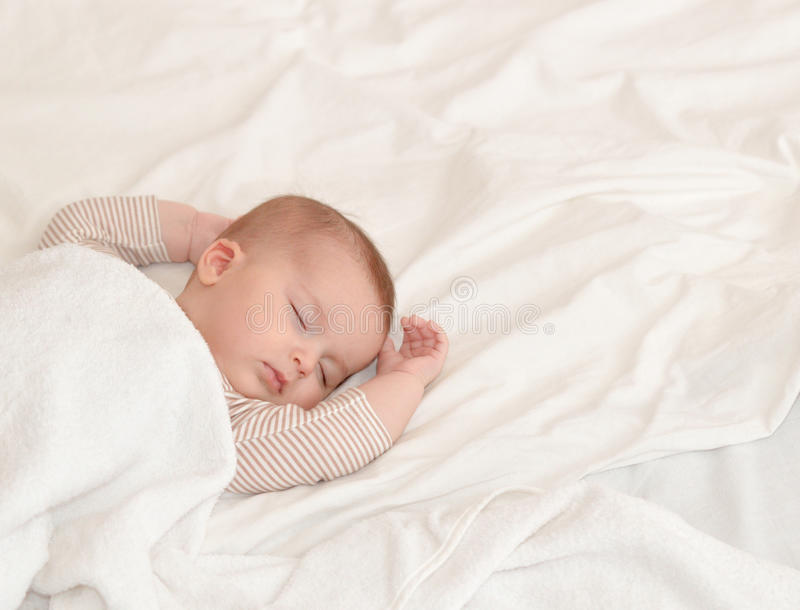 Peaceful baby lying on a bed while sleeping in a bright room stock image
