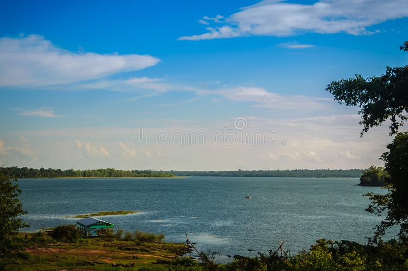 Peaceful blue lake with green grass and blue sky background. Beautiful blue sky and clouds over the reservoir. Rafting activity i. N the still water lake under stock photography