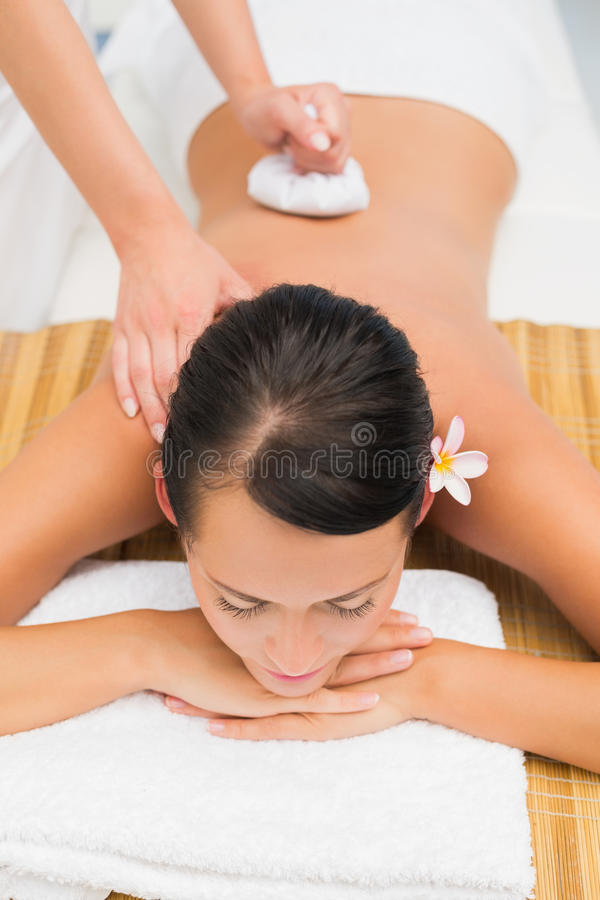 Peaceful brunette enjoying a herbal compress massage. In the health spa royalty free stock image
