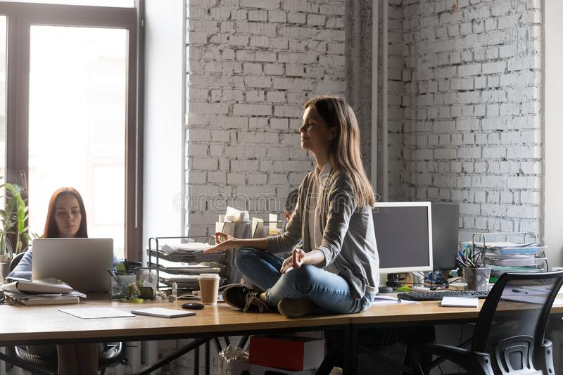 Peaceful businesswoman meditating on office desk, stress relief concept. Peaceful businesswoman meditating with closed eyes on office desk, young intern stock images